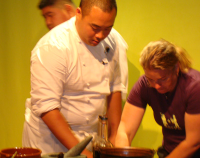 An assistant helps New York chef David Chang prepare for his cooking demo.
