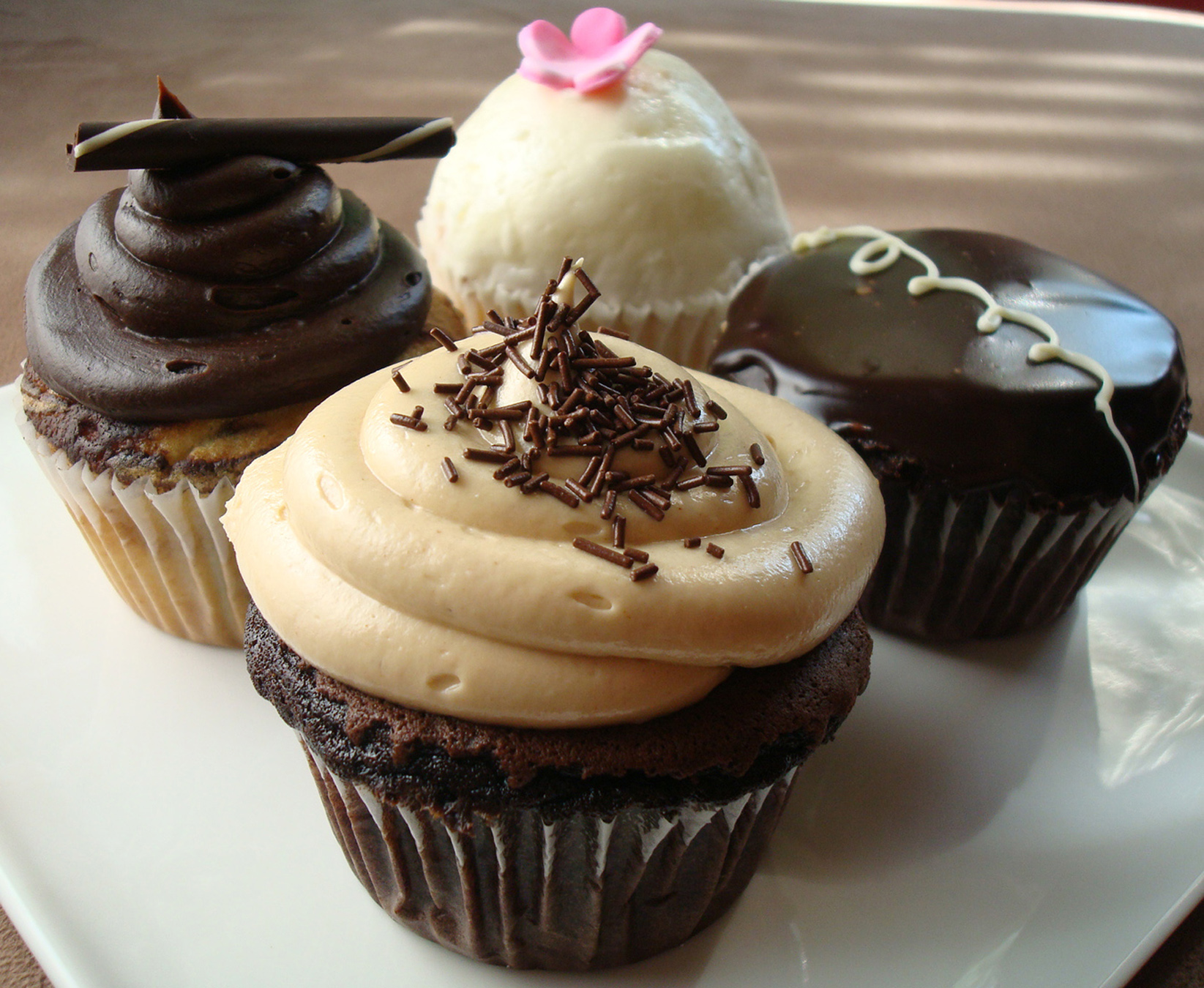 Clockwise from back: Strawberry-filled vanilla, chocolate, peanut butter-filled chocolate, and marble cupcakes.