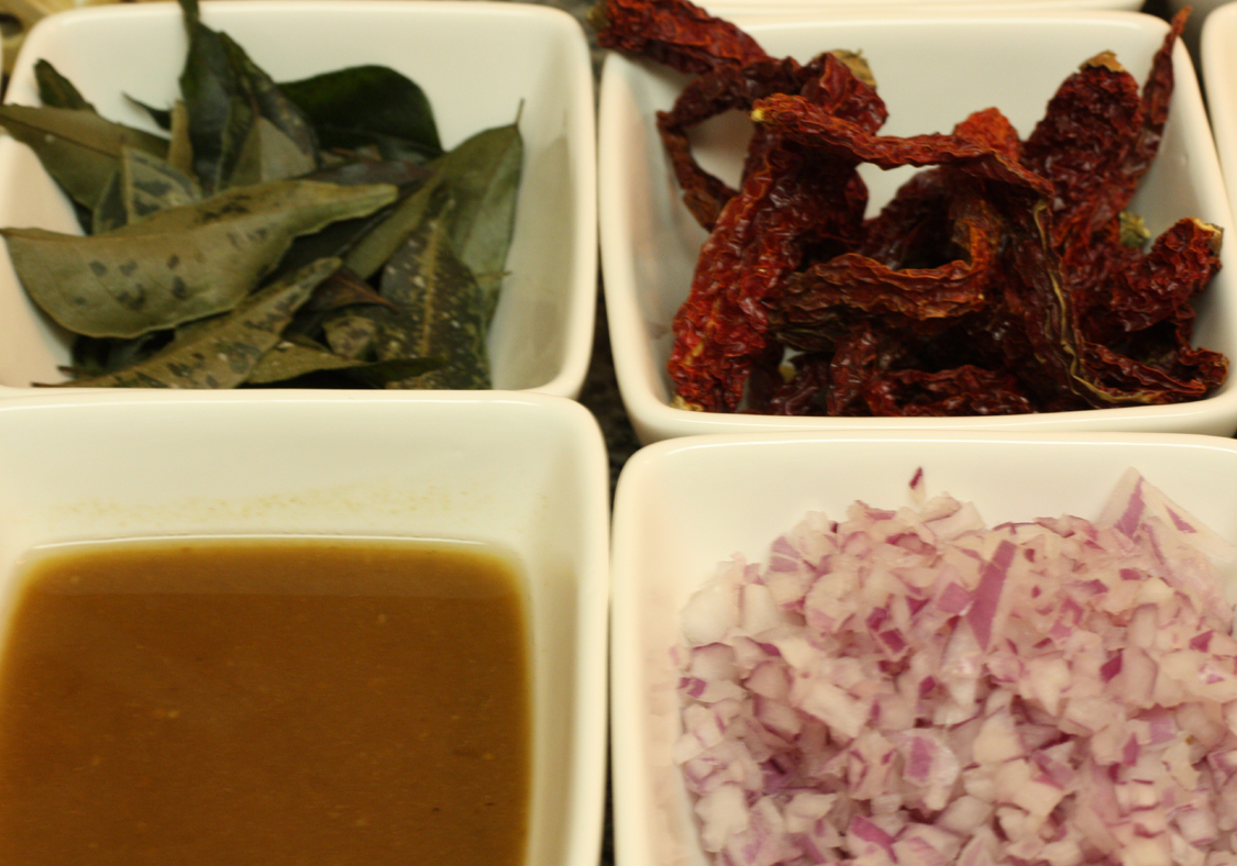 Some of the ingredients for the curry dish: (back, from left to right) curry leaves and Byadagi chilies; (front, left to right) tamarind juice and chopped red onions.