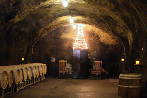 The warm glow of a Christmas tree lights the way inside the ancient Beringer Vineyards wine caves.