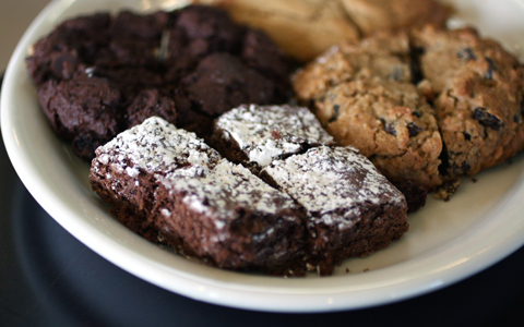 "Brownies, double-chocolate cherry cookie, peanut butter cookie, and ""Mom's Oatmeal Raisin'' cookie -- cut up in this photo for sharing."