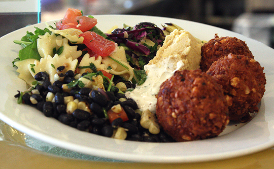 A vegetarian entree of falafel, hummus, pasta salad, and black bean salad.