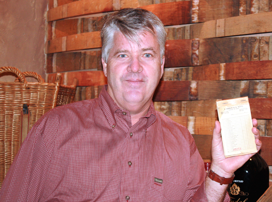 Winery owner John Tudal, holding up an old receipt from his family's produce farm.