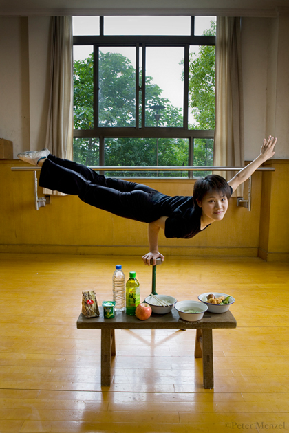 Cao Xiaoli, a professional acrobat, balances on one hand with her day's worth of food at Shanghai Circus World in Shanghai, China. (From the book What I Eat: Around the World in 80 Diets.) The caloric value of her day's worth of food on a typical day in June was 1700 kcals. She is 16 years of age; 5 feet, 2 inches tall; and 99 pounds. Cao Xiaoli lives in a room with nine other girls. She started her career as a child, performing with a regional troupe in her home province of Anhui. Now she practices five hours a day, attends school with the other members of her troupe, and performs seven days a week. She says what she likes best about being an acrobat is the crowds reaction when she does something seemingly dangerous. MODEL RELEASED.