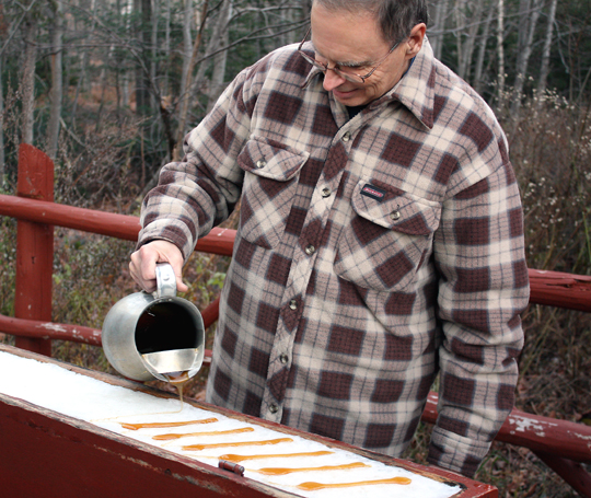 Maple syrup being poured on a bed of snow.