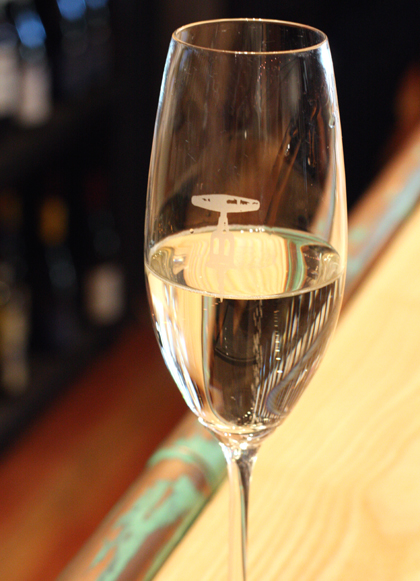 A glass of prosecco, emblazoned with a corkscrew insignia.