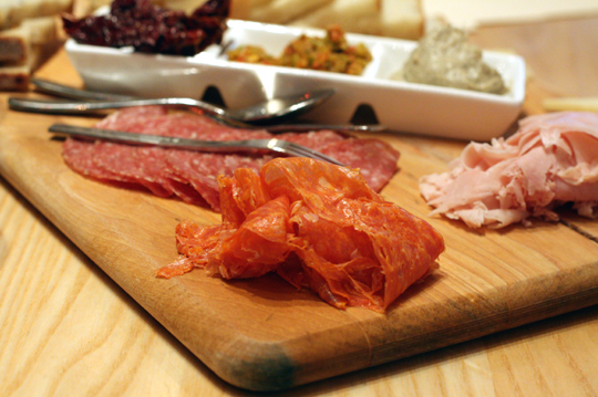 A bountiful sampler board of cheeses, cured meats and spreads.