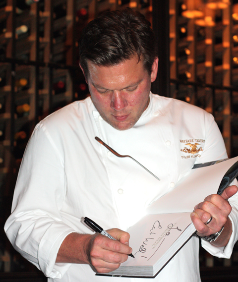 Tyler Florence autographs one of his cookbooks at his Wayfare Tavern.
