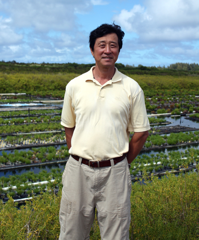 Wenhao Sun stands before his hydroponic farm.