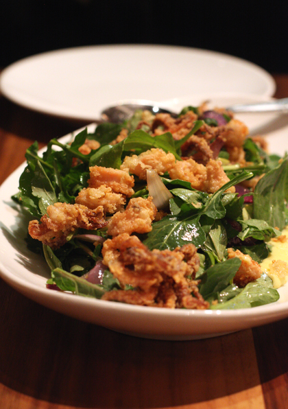 Crunchy, fried calamari tops argula leaves.