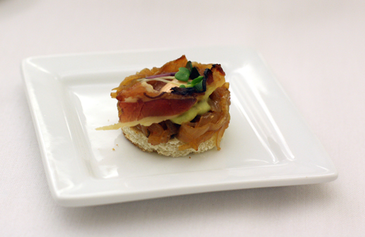 An amuse of crisp crostini topped with bacon and caramelized shallots.