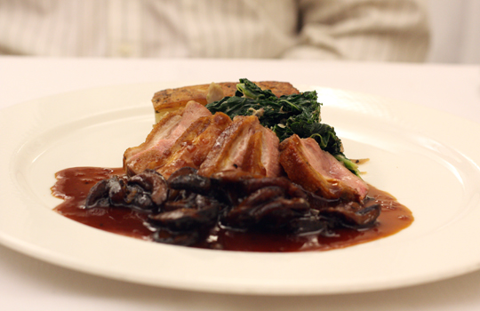 A beautifully cooked duck with kale.