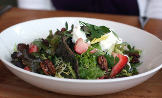 Green salad with spiced pecans and strawberries.