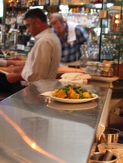 A plate of food ready to be served. The bar is in the background.