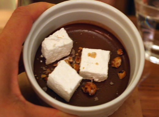 A chocolate pot de creme with marshmallows and candied hazelnuts.