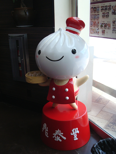 The Din Tai Fung dumpling mascot greets you at the door.