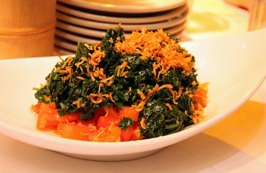 Tomato and spinach salad strewn with fried shallots.