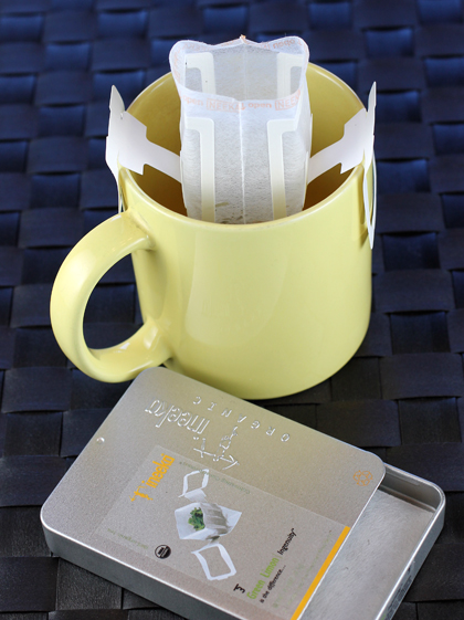 The top of the bag opens up to allow water to be poured into it. Handles on the bag fit on the lip of your mug to hold it in place.