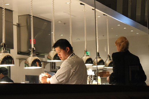 Executive Chef Yu Min Lin expedites at the glass-fronted open kitchen.