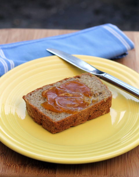 A slice of gluten-free bread fresh out of the oven that's smeared with Mango fruit spread.