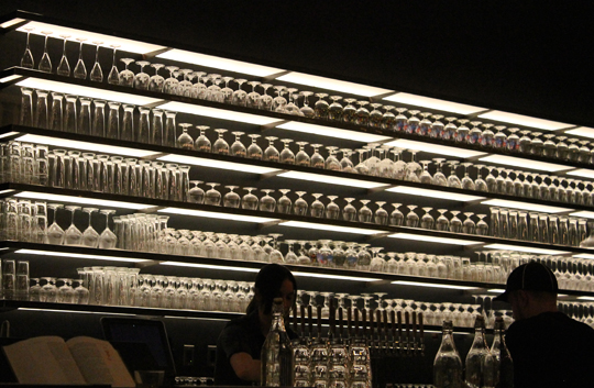 An eye-catching back-lit wall of beer and wine glassware behind the bar.