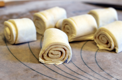 Purchased puff-pastry is thawed, then rolled up jelly roll-style before being sliced into six equal portions.