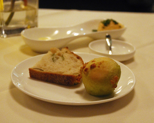 A selection of breads, including olive and a pesto popover, served with butter, as well as paprika-garlic cream cheese.