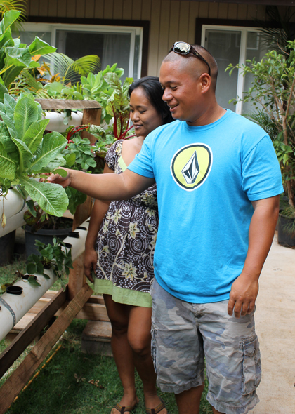 Monica Bogar and Chef Isaac Bancaco inspect one of Bogar's aquaponics systems.