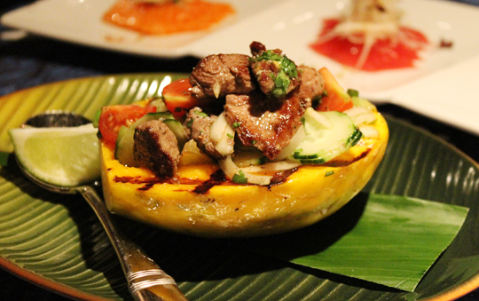 Seared beef in a grilled papaya half.