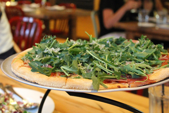 Pizza with prosciutto and arugula.