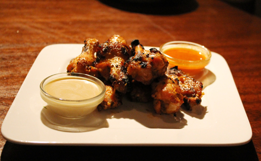 Chicken wings with two dipping sauces.