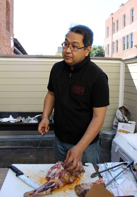 Chef Dave Cruz cooking a whole lamb at his pop-up event.