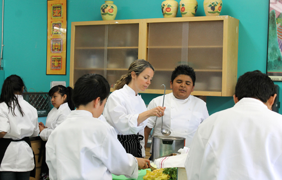 Chef Amy Glaze teaching young students how to cook.