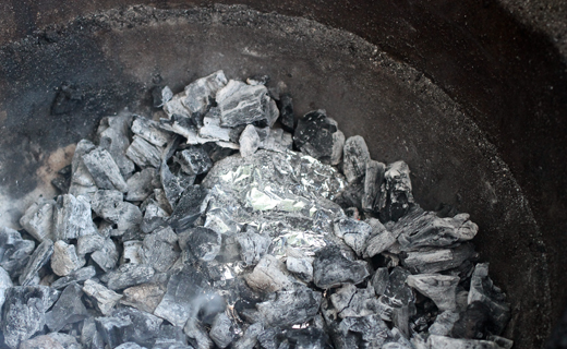 The foil packets get buried in embers for an hour.