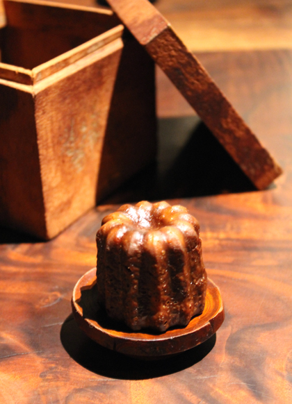 Caneles in a fragrant cinnamon box.