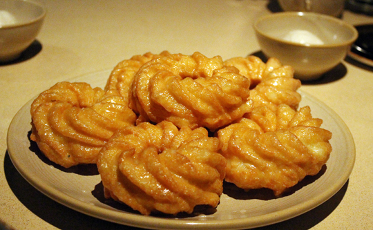 French crullers fresh out of the fryer.