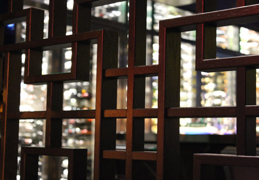 The soaring wine room as seen through the artsy wood divider.
