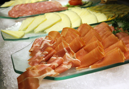 A spread of cheeses and cured meats at the salad bar.