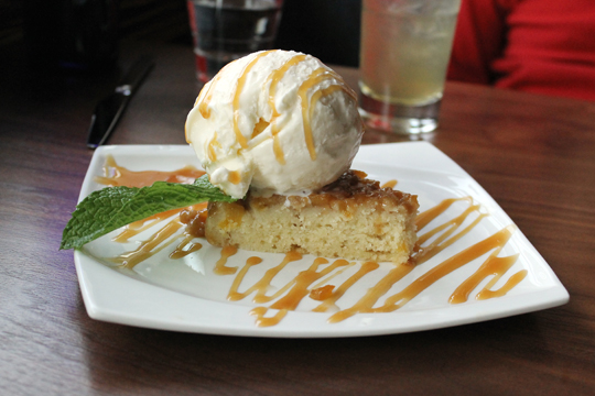 A wedge of mango cake with an outsized scoop of coconut ice cream.