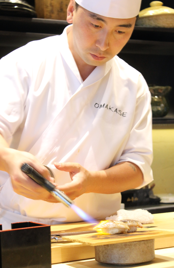 Chef Justin Yu behind the bar at Omakase.