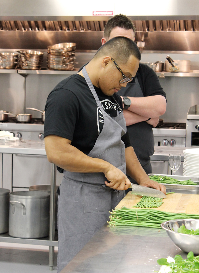 Chef Johnny Madriaga cutting up long beans.