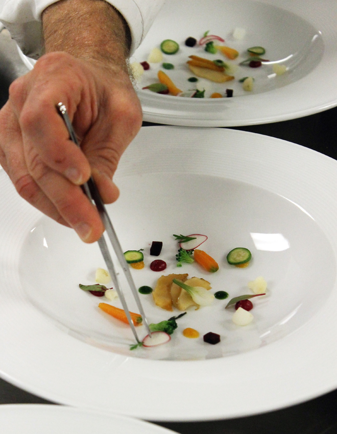 Plating garnishes for the vegetable consomme with abalone.