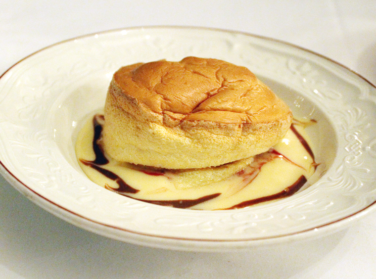 The souffle served atop creme anglaise and raspberry coulis.