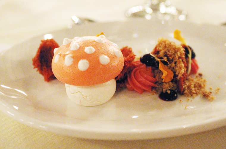 A cute meringue mushroom is the centerpiece of this dessert.