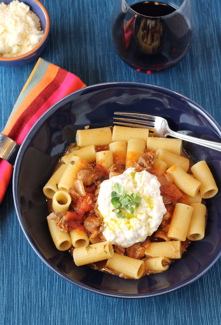 Whipped ricotta with a drizzle of extra-virgin olive oil finish this lamb ragu with rigatoni.