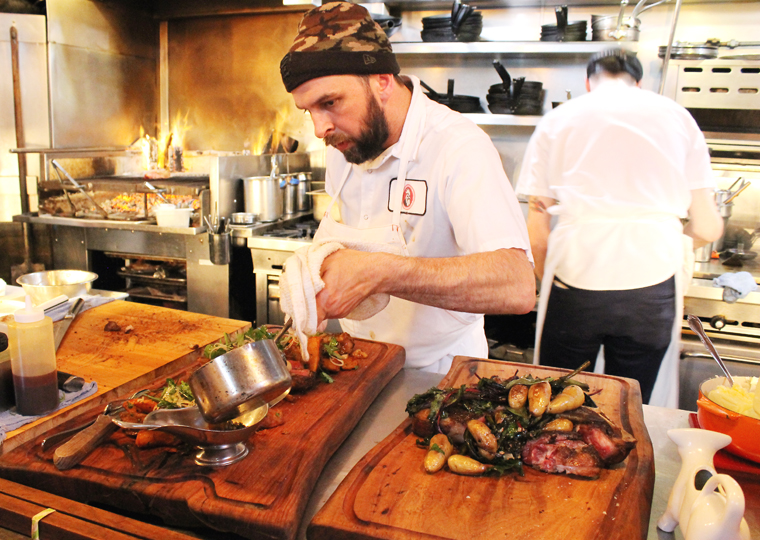 A cook prepares a huge platter of meat, meant to be shared (of course!).