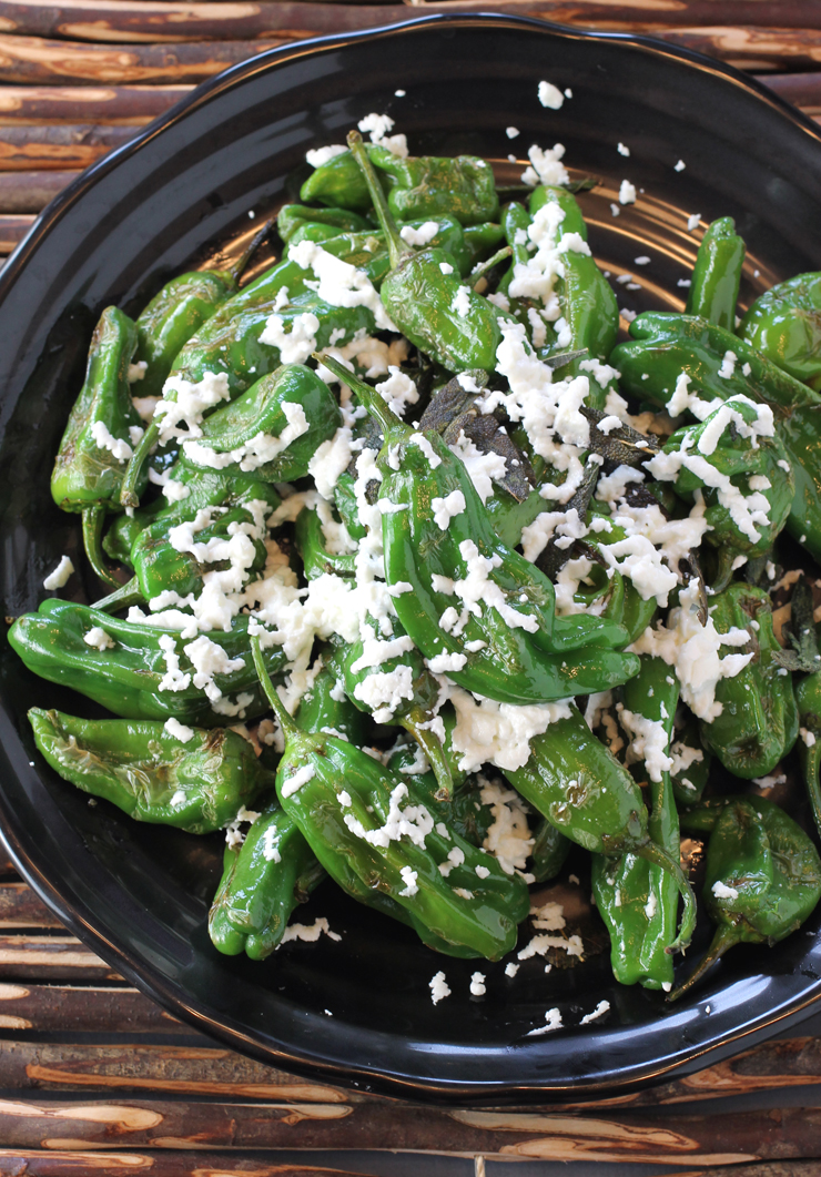 A pile of just-seared shishitos gets dressed with lovely goat cheese and sage leaves.
