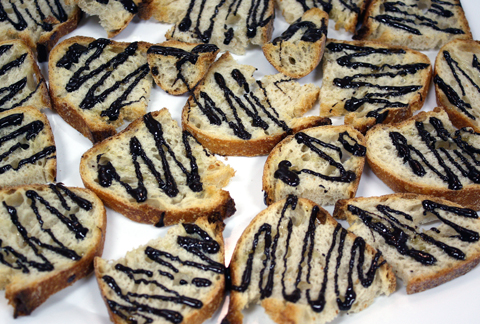 A tapa of rustic bread drizzled with dark chocolate, olive oil, and sea salt.