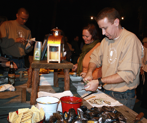 Shucking the roasted oysters, which are dumped out on a wooden table to help yourself to.