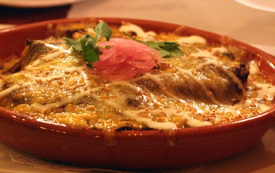 Enchiladas covered in mole sauce.